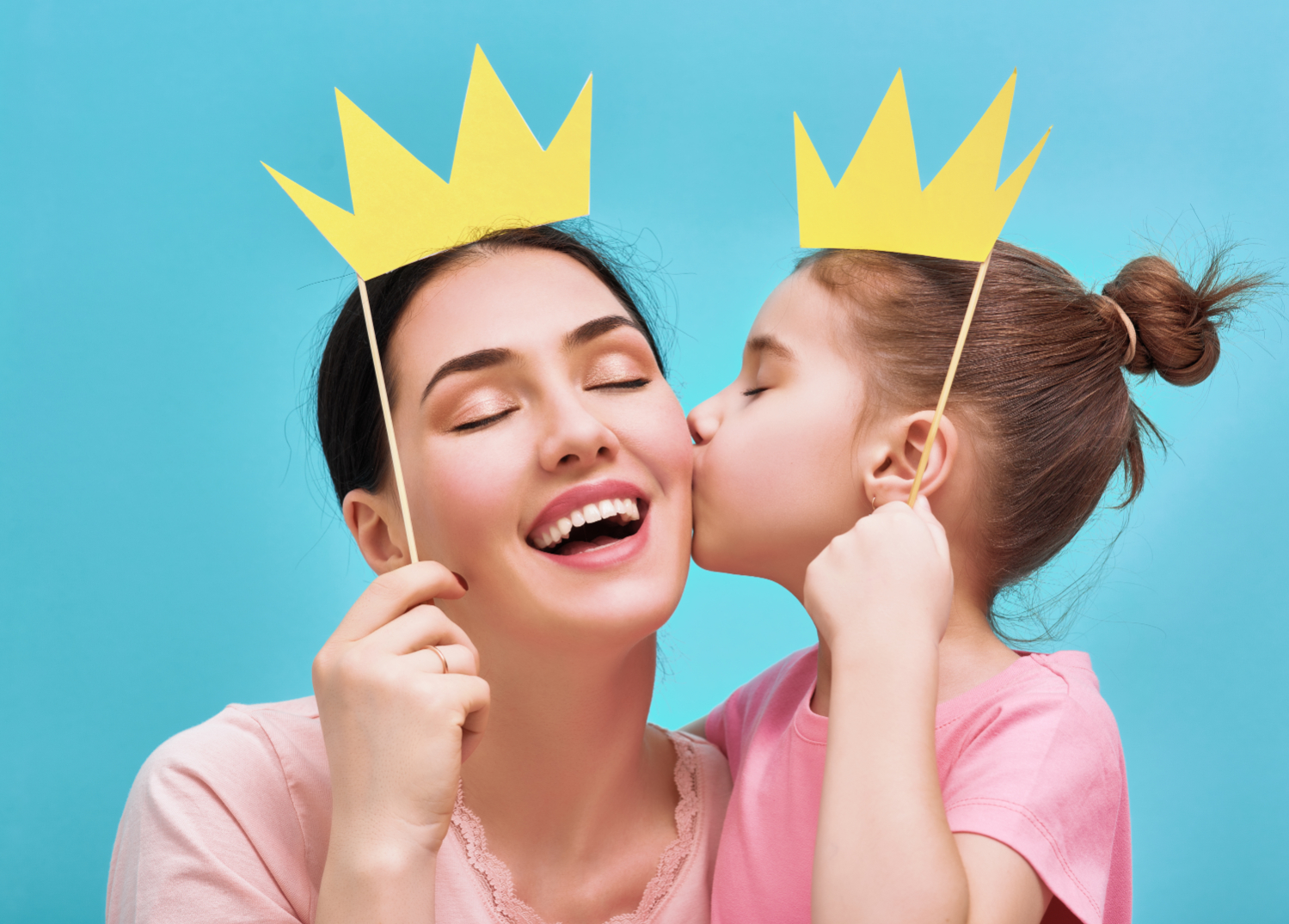 Mom and child holding paper crown on stick. Mom laughing